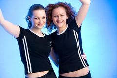 Super!. Two girls in black T-Shirts are jubilating shoulder-to-shoulder Stock Photo