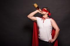 Super antiheldenmens het drinken alcohol Stock Fotografie