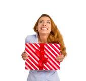Super aufgeregte flippige Frau mit der Geschenkbox, die oben weißen Hintergrund schaut Stockbilder