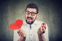 Super aufgeregter Mann mit rotem Herzform-Eheringkasten lizenzfreie stockfotos