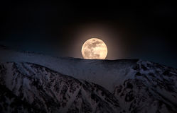 Super big Moon rises over snow capped mountains at twilight. Close up view of rising moon at night. Super big Moon rises over snow capped mountains at twilight Stock Photo