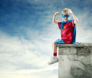 Super bohatera chłopiec z nastroszonymi pięściami Obrazy Stock