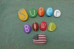 Super bowl text with colored stones and Usa flag over green sand. Super Bowl, annual championship game of the National Football League, where the champion of the royalty free stock image