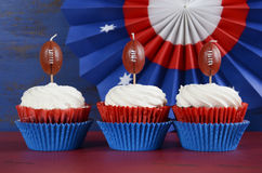 Super bowl cupcakes. Red, white and blue theme cupcakes with football toppers for Super Bowl Sunday party or collage football finals and playoffs stock photography