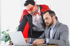 Super businessman in mask and cape helping businessman with work. In office stock photo