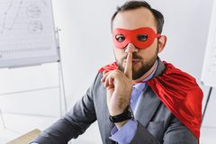 Super businessman in mask and cape showing silence sign. In office stock photography