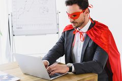 Super businessman in mask and cape working with laptop. In office stock photography
