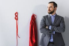 super businessman standing with crossed arms near mask and cape on wall royalty free stock photography