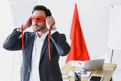 Super businessman tying red mask. In office stock images