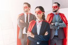 Super businesspeople in masks and capes looking away with crossed arms. In office royalty free stock photos