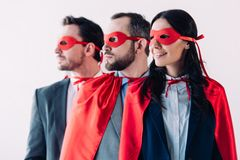 super businesspeople in masks and capes looking away in line stock image