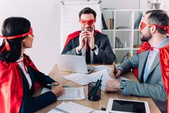super businesspeople in masks and capes at meeting royalty free stock images