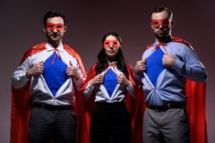 Super businesspeople in masks and capes showing blue shirts. Isolated on grey stock images
