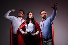 Super businesspeople in masks and capes showing superpower. On grey royalty free stock photos