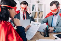 Super businesspeople in masks and capes working. In office royalty free stock image