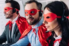 Super businesspeople in masks and headsets supporting customers. In call center royalty free stock photography