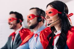 Super businesspeople in masks and headsets supporting customers. In call center royalty free stock images
