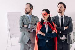 super businesswoman standing with crossed arms in mask and cape with businessmen stock photos