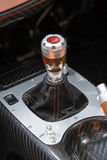 Super car gear stick with red start button. On carbon fibre surround Stock Photos