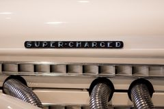 Super-charged. Retro engine mock-up with art deco super charged. Super-charged. Retro engine mock-up with the words super charged. Cream paint and chrome pipes stock images
