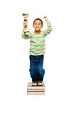 Super clever nerd winner. Clever black boy standing on pile of books and holding winner cup as he wins competition royalty free stock images