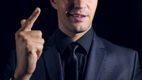 Super close-up of a man in black clothes on a black background. 4k. Slow motion. stock video