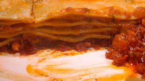 Super close-up a piece of the delicious lasagna. Super close-up a piece of the delicious Italian lasagna taken out with a spatula stock video