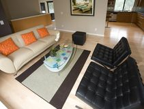 Super Contemporary Living Room. Black leather barcelona chairs, tan leather couch, glass coffee table, tan and brown throw rug, maple wood flooring, orange wall Stock Photography