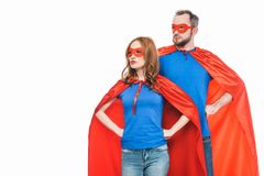 super couple in masks and cloaks standing with hands on waist and looking away royalty free stock photo