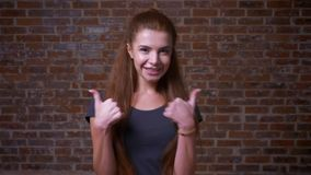 Super cute caucasian ginger girl is standing and dancing with two like fingers, showing her perfect mood and sighns of. Super cute caucasian ginger girl is stock video
