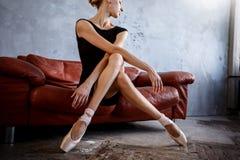 Super dünne Ballerina in einem schwarzen Kleid wirft im Studio auf Stockfotos
