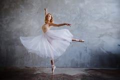 Super dünne Ballerina in einem schwarzen Kleid wirft im Studio auf Stockfoto