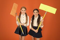 Super duper cleaning. Cute schoolgirls holding floor mops. School children with cleaning tools. Little girls ready for