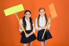 Super duper czyścić Śliczne uczennicy trzyma podłogowych kwacze Dzieci w wieku szkolnym z czyści narzędziami Małe dziewczynki got zdjęcie stock