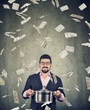 Super excited man with boil pan under money dollar bills rain. Content super excited man with boil pan under money dollar bills rain on gray wall background royalty free stock photography