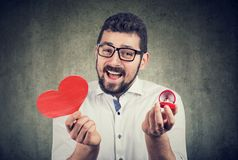 Super excited man with red heart shape wedding ring box. Romantic proposal concept royalty free stock photos