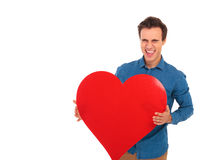 Super excited young casual man laughing and holding a  heart Royalty Free Stock Photography