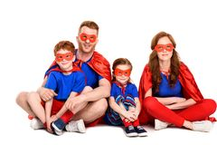 Super family in costumes sitting together and smiling at camera. On white stock image
