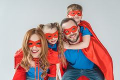 Super family in masks and cloaks having fun together and smiling at camera. Isolated on grey stock images