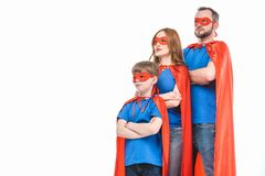 Super family in masks and cloaks standing with crossed arms and looking away. Isolated on white royalty free stock photography