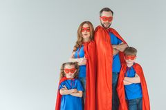 Super family in masks and cloaks standing with crossed arms and looking at camera. Isolated on grey royalty free stock image