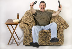 Super Fan. Man sitting on stuffed chair with TV remotes in hands and cheering Stock Photography