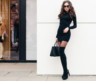 A super fashionable long-legged brunette girl with long hair dressed in a short black dress, black high heels with a Stock Photo