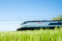 Super fast passenger train. Italian Eurostar train running beside the cultivate lands royalty free stock images