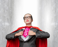 She is super financier. Young woman acting like super hero with dollar sign on chest stock photography