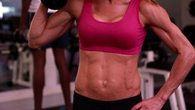 Super fit woman lifting dumbbells in pink sports bra. At the gym stock video footage