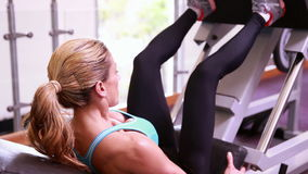 Super fit woman using the leg weights machine stock video
