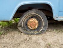Super flat old tire:. Close up a an old car`s flat tire Stock Photos