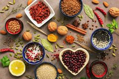 Super food background, a variety of cereals, legumes, spices, herbs, nuts. Various seasonings for cooking on brown background. Top stock photos
