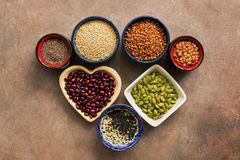 Super food cereals, legumes, seeds on a brown background. Chia, quinoa, beans, buckwheat, lentils, sesame, pumpkin seeds. Top view stock photo